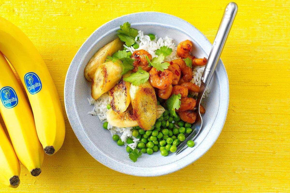Gebakken, gemarineerde garnalen. Met doperwten, rijst en gebakken banaan