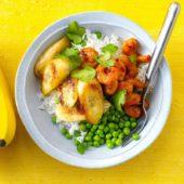 Gebakken, gemarineerde garnalen met doperwten, rijst en gebakken banaan